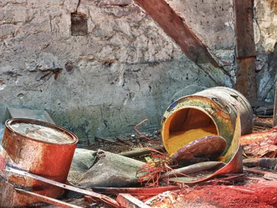 A barrel full of chemical waste lies where a textile factory was demolished. Photo source: Getty Image.