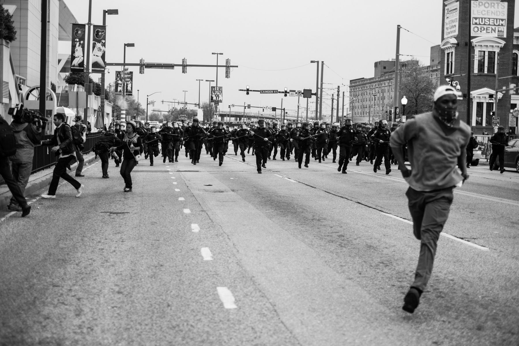 Devin Allen's image of a man running from a phalanx of Baltimore Police.