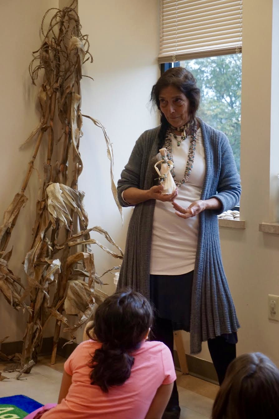 Photo by Elif Ronning, Media Intern Vickie Raabin holds up a finished corn husk dolls as an example.