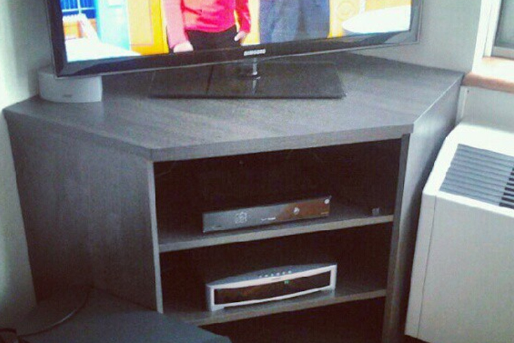 Corner TV stand with component storage.