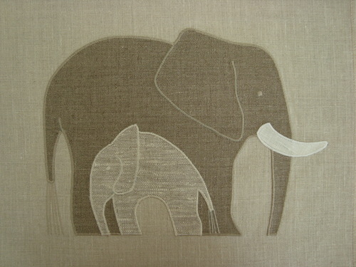 """A sheltering mother elephant above in Irish Linen and Enzyme Washed Linen and cream. The Elephant Mother applique is 12"""" wide. $36.00 per motif."""