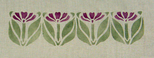 Iris Two Bor  de r :  R epeat of 1 1/2 inches high x 3 inches wide, shown here in purple and sage on natural linen. $40.00 per repeat