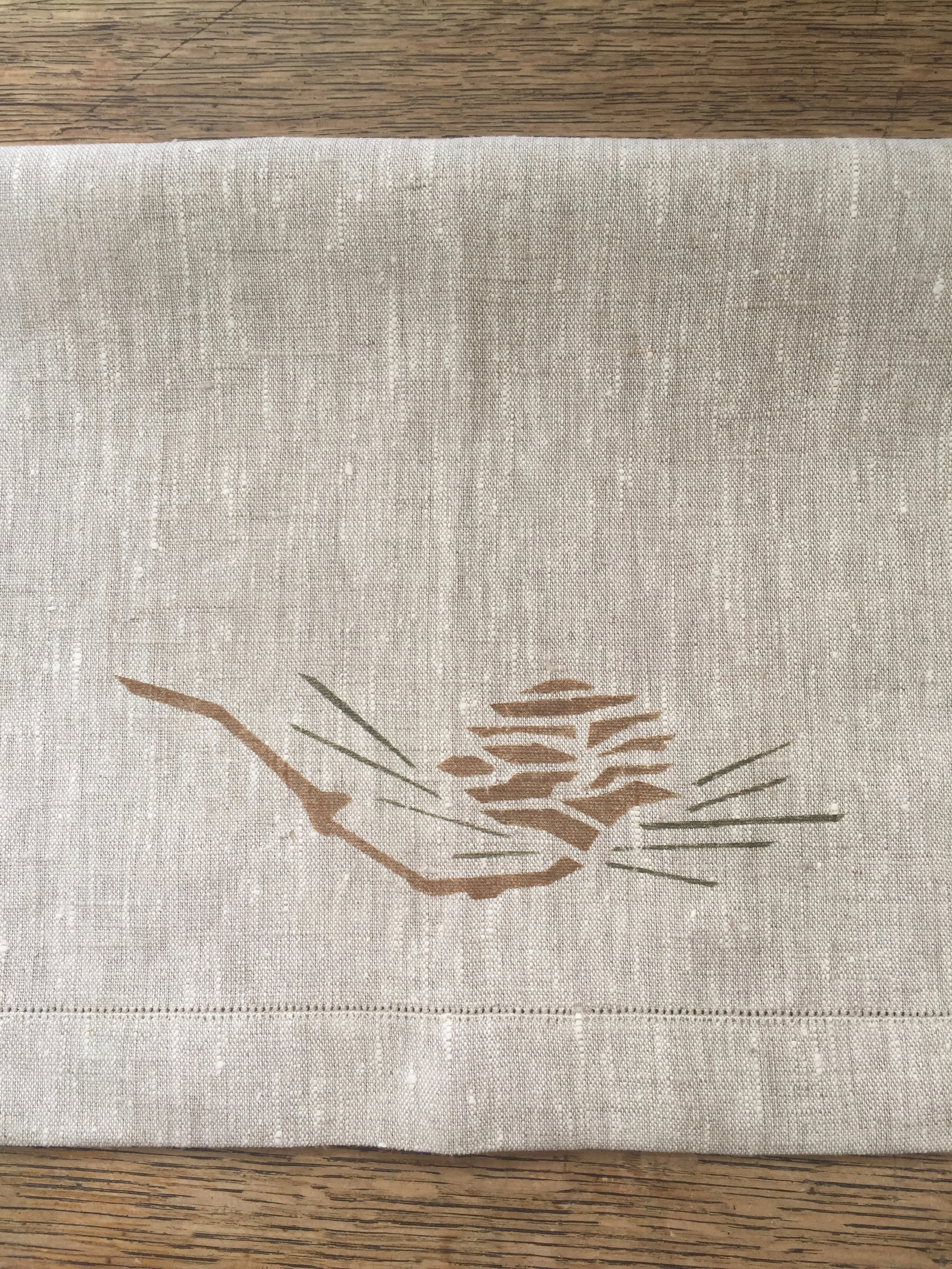 Pine Cone Two Border stencil. A popular motif in whiskey and loden on a custom napkin with pin stitch hem.