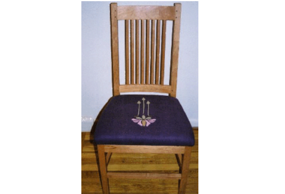 A craftsmen dining chair upholstered in appliqued linen.