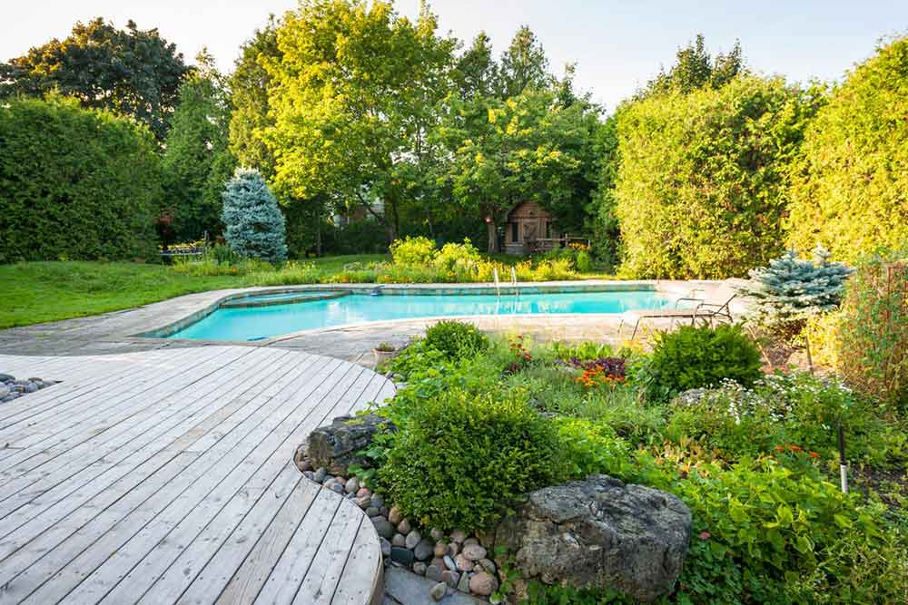 deck by pool with landscaping
