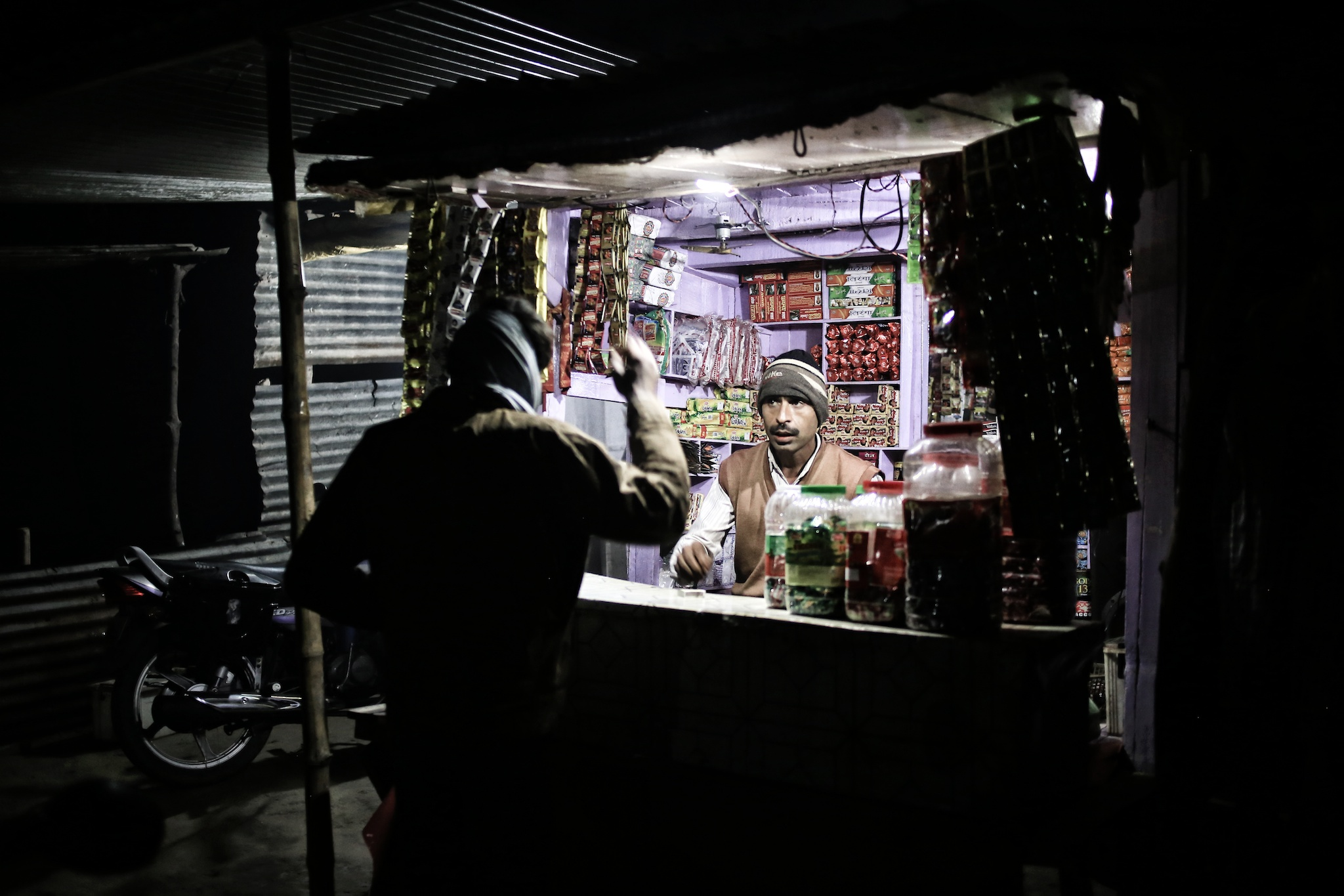 Small kiosk lit up by microgrid solar. Photo via SunFunder