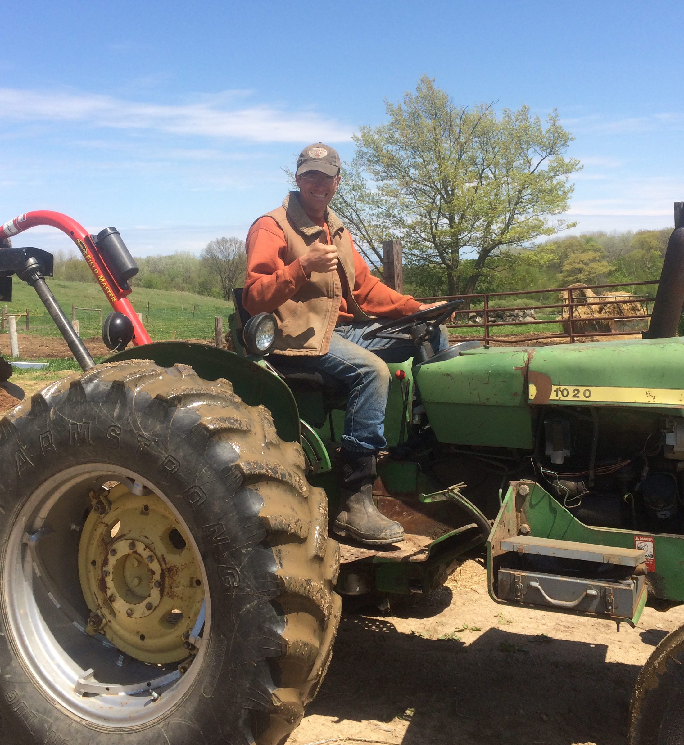 a happy farmer on his tractor on a beautiful day
