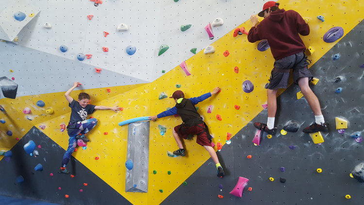 Trenton, Parker, and Nevin practice teamwork in an elevated state at Spire Climbing Center.