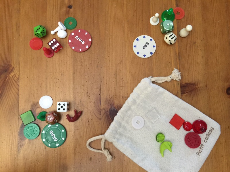 Grab Bag showing player poker chips with betting on them, and their respective collected tokens (which shows Red and Green tied as winners of the Grab, with 7 tokens each), and the results in the bag as the leftover tokens (which shows that Red wins the Bag)