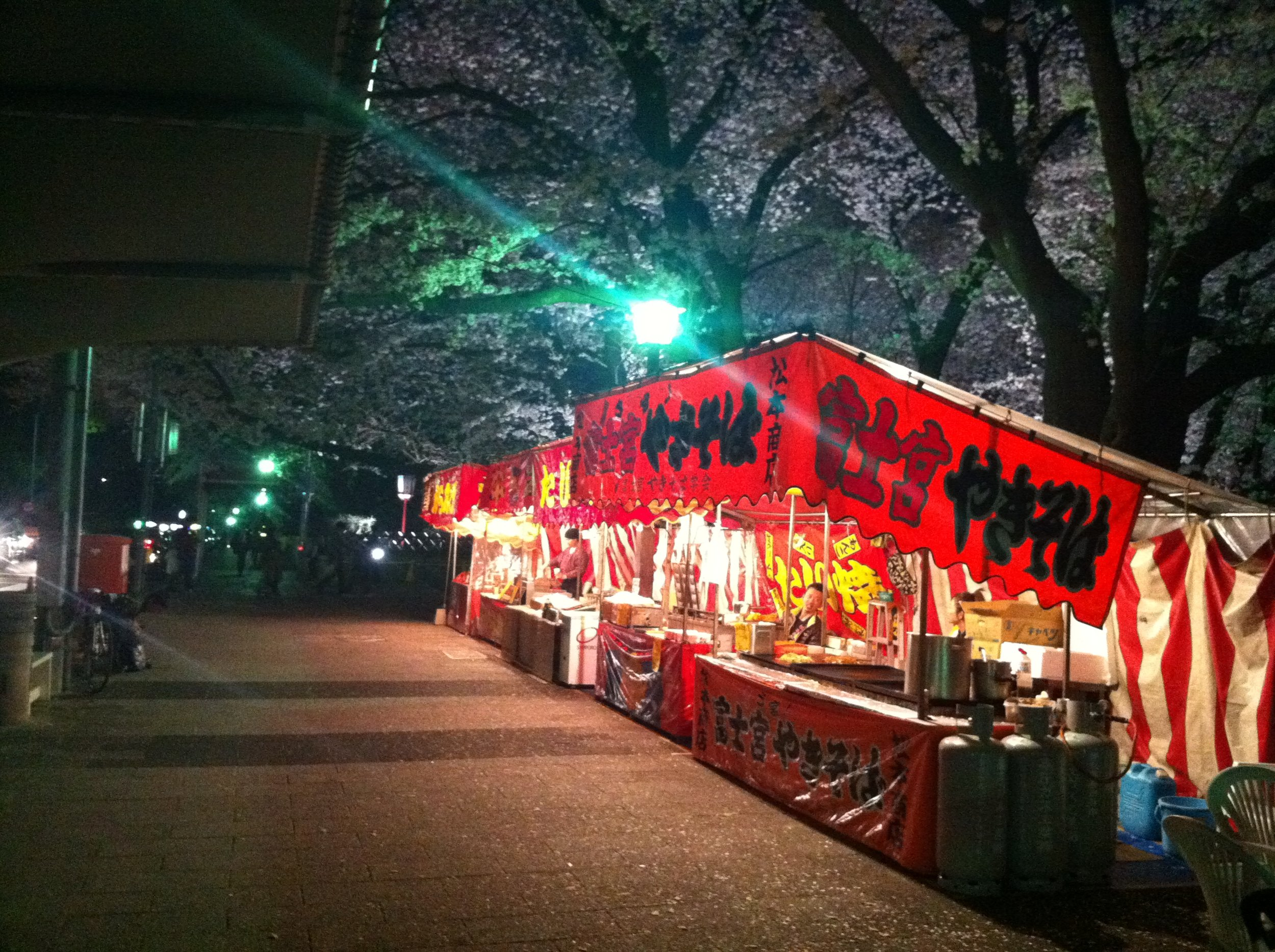 "Left: A ""light-up"" at Nagoya Castle during cherry blossom season. Right: a food stall with cherry trees."