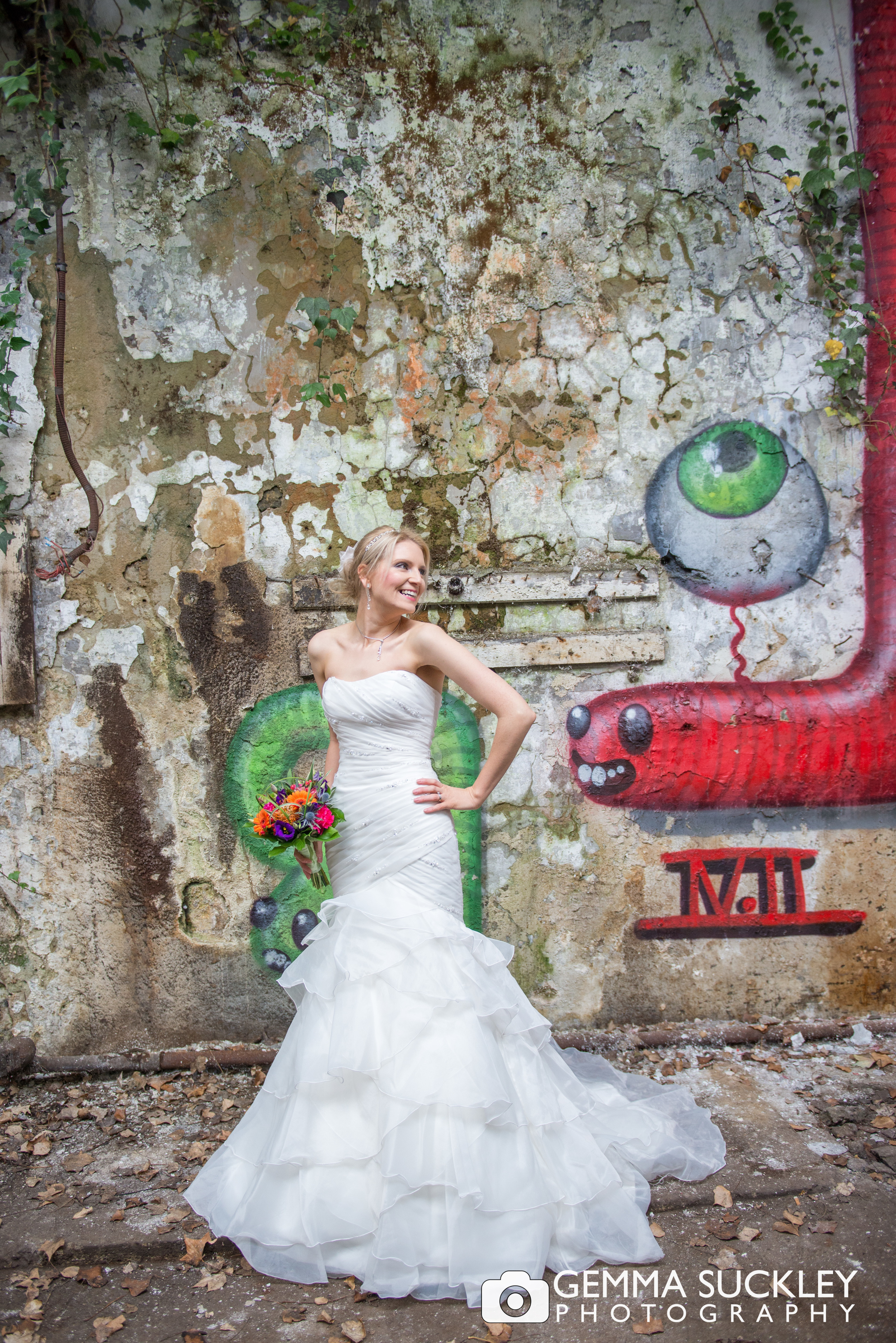 bride posing with graffiti behind her