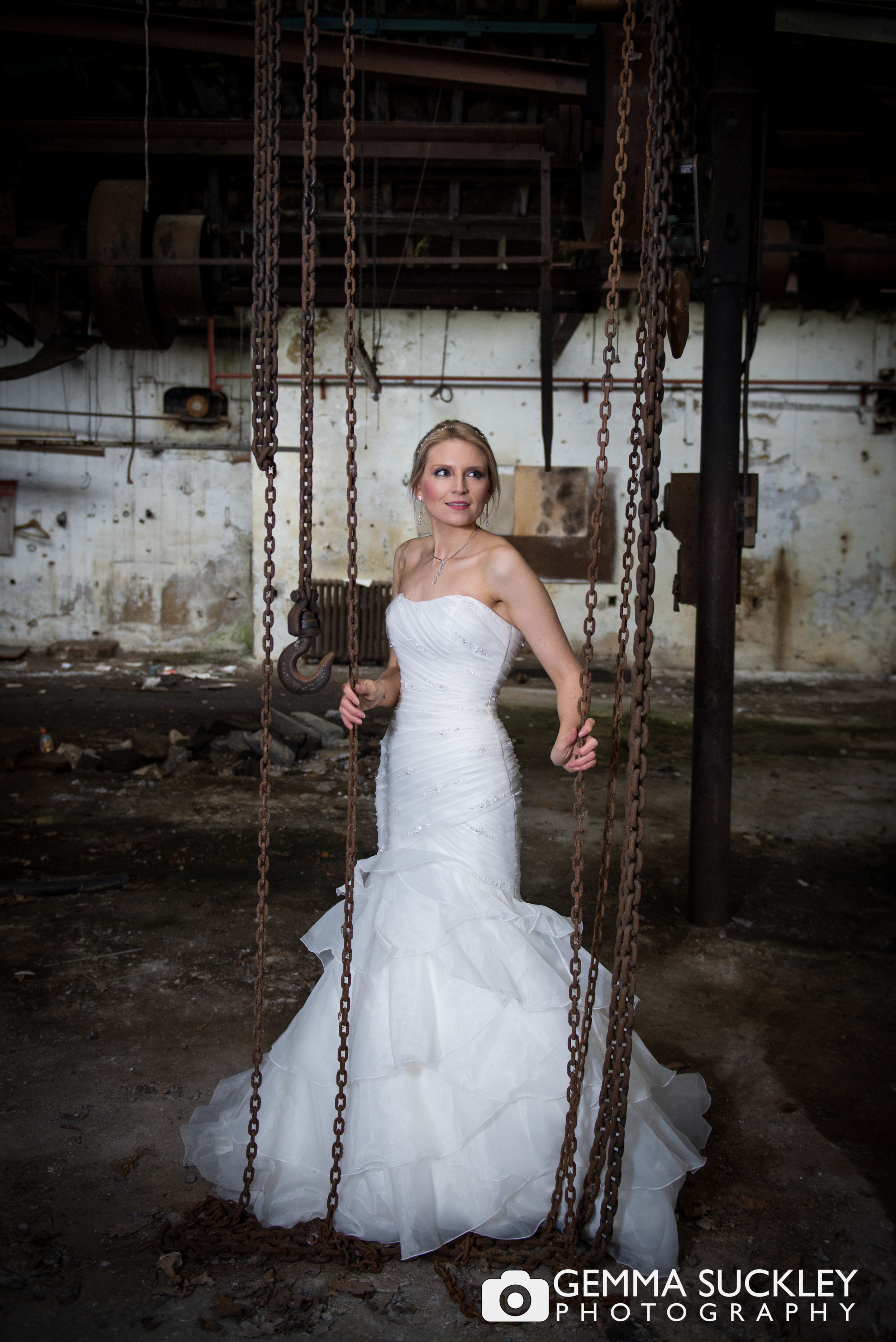 bride posing in a dirty abandoned mill