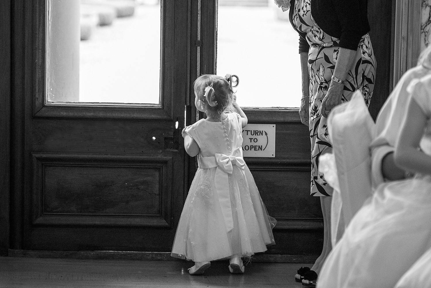 Copy of flower girl peeking out the window during a wedding
