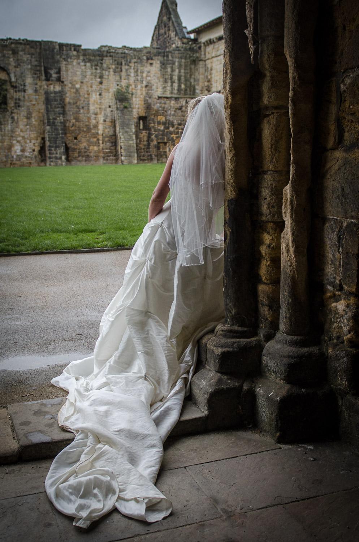 moody photo of a bride and dress train at kirkstall abbey