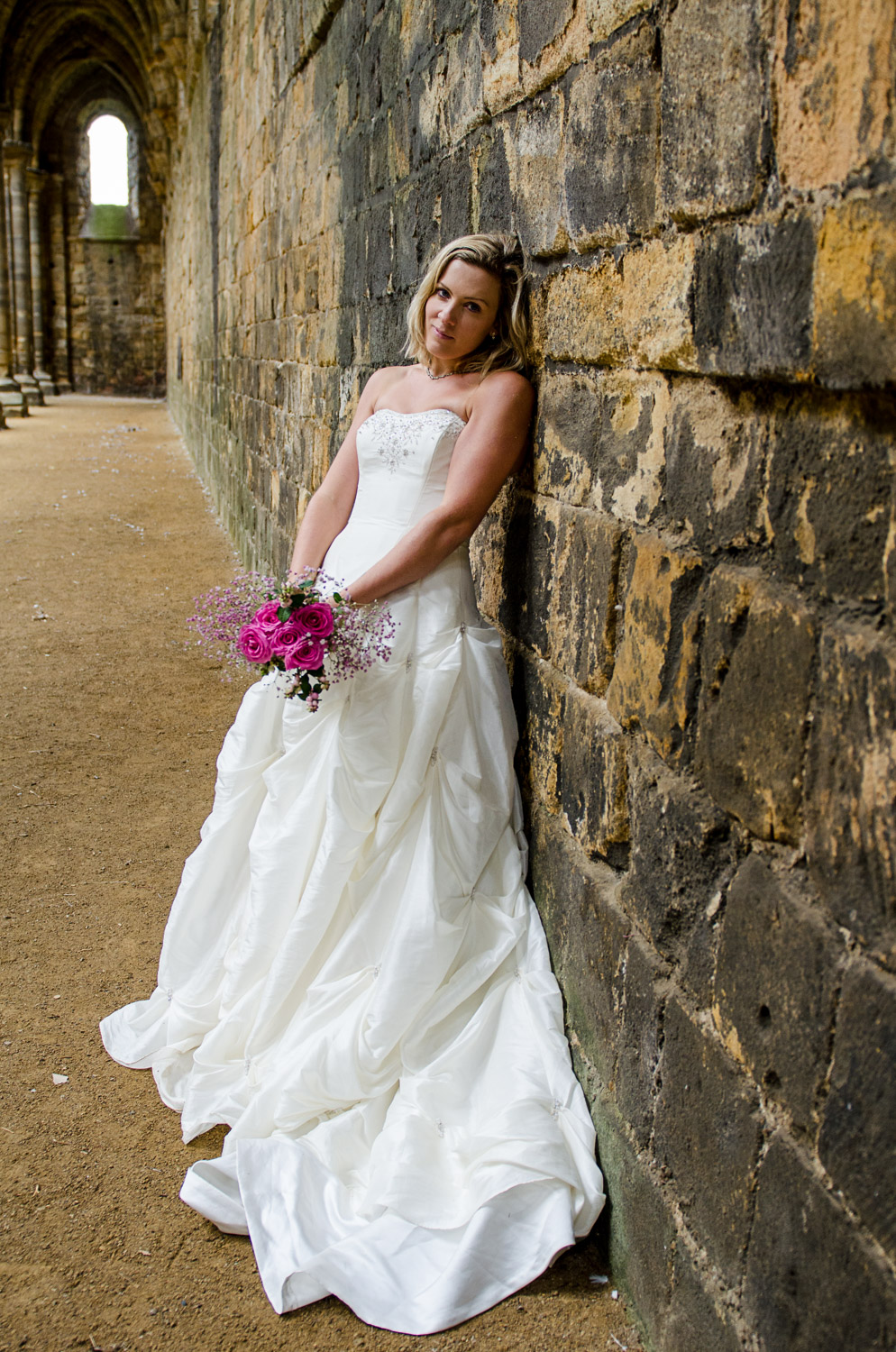 bride with flowers at kirkstall abbey