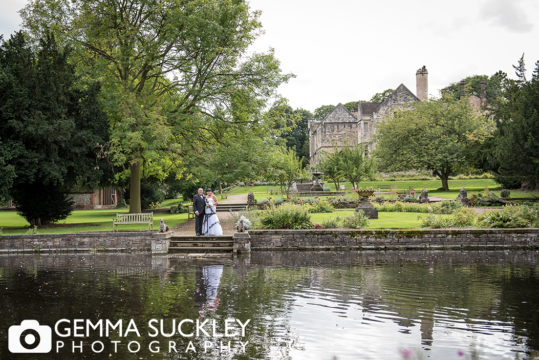 bride and groom by the lake at Monk Fryston Hall Hotel on their wedding day