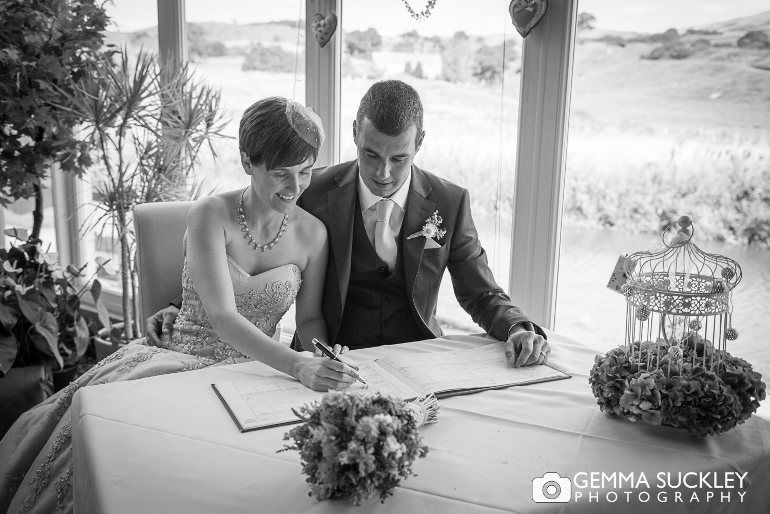 newly-weds signing the wedding register in rendezous