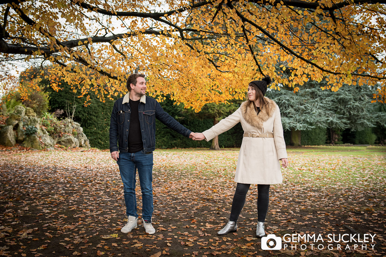 A couple holding hands in autumn at Hazlewood Castle