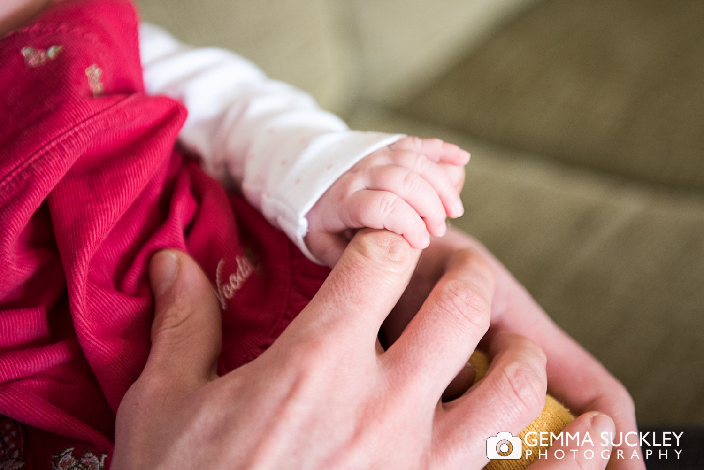 newborn baby holding dad's finger