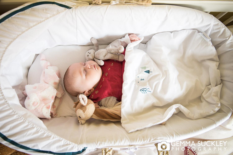 a newborn baby sleeping in her cot