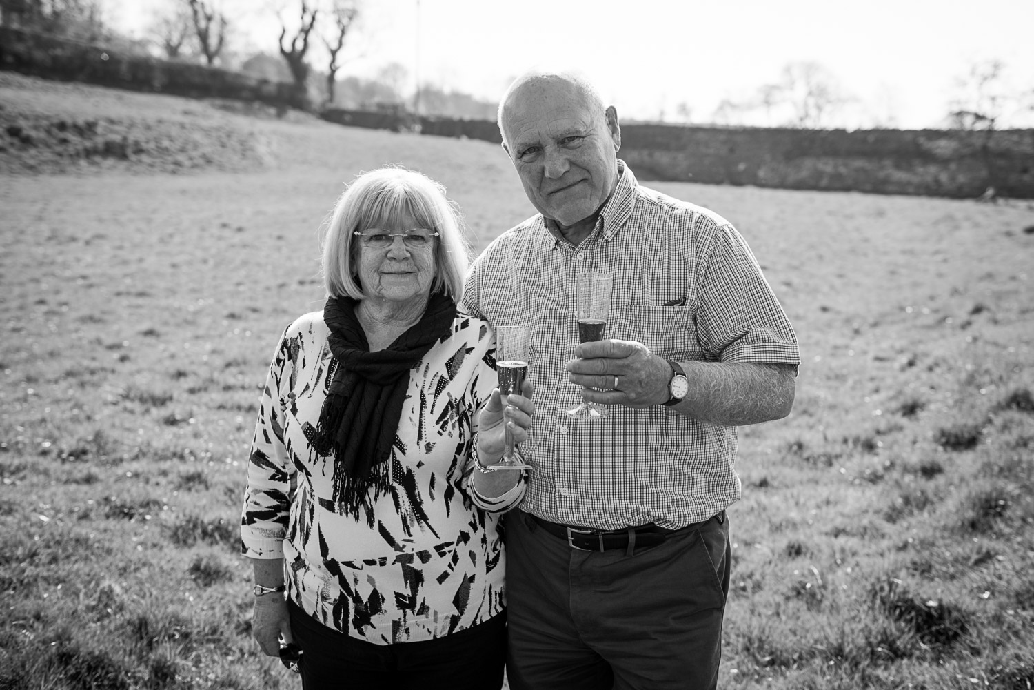 black and white photo for a couple cheersing with champagne