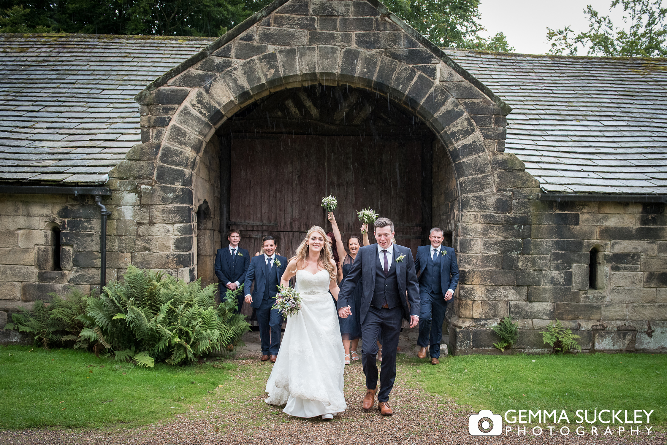bride and groom in the rain at east riddlesden hall