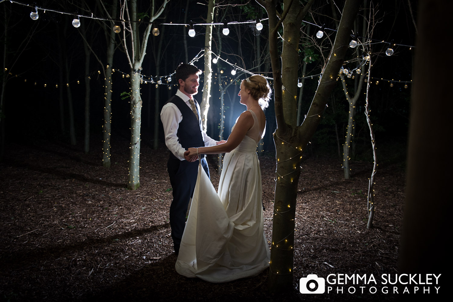 bride and groom surrounded by back-lit fairy lights