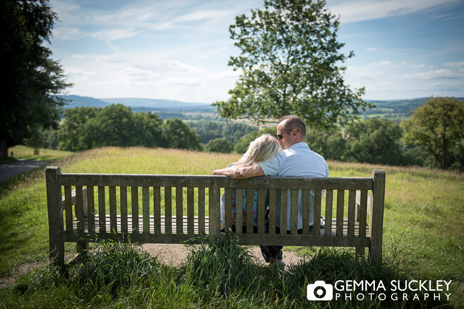 a couple sat hugging on a bench at harewood house