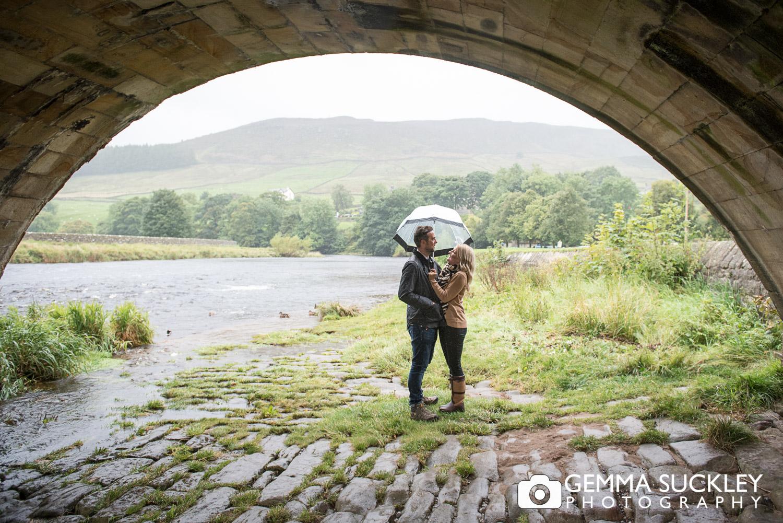 couple with an umbrella under burnsall bridge