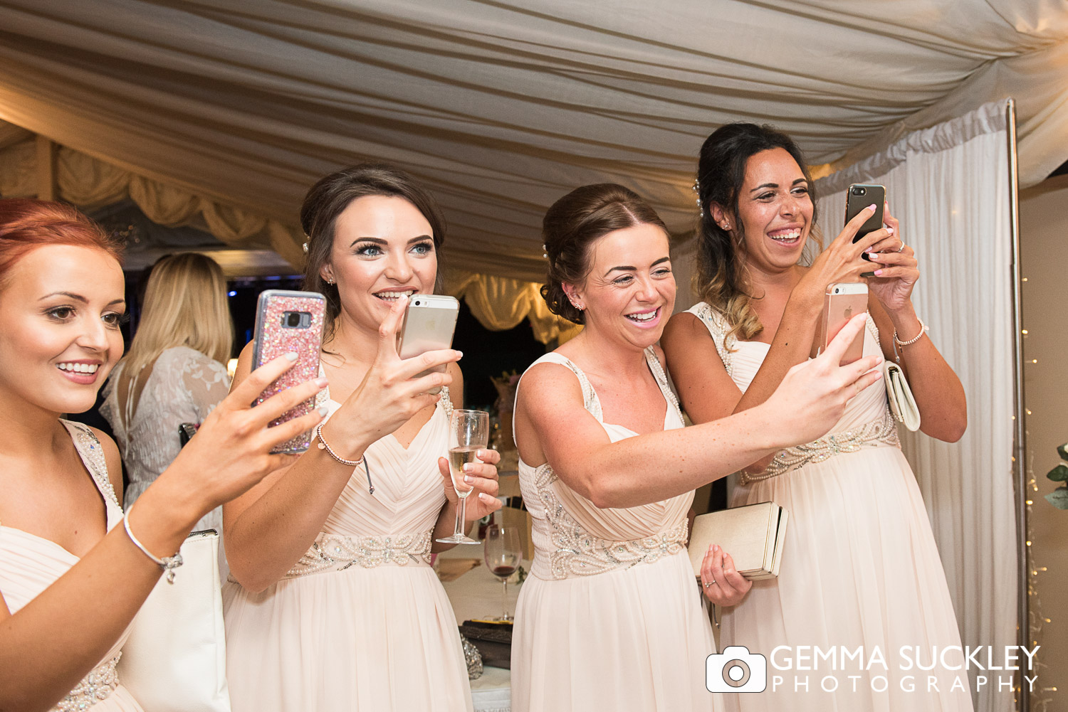 bridesmaids taking photos on their mobiles at moorlands inn