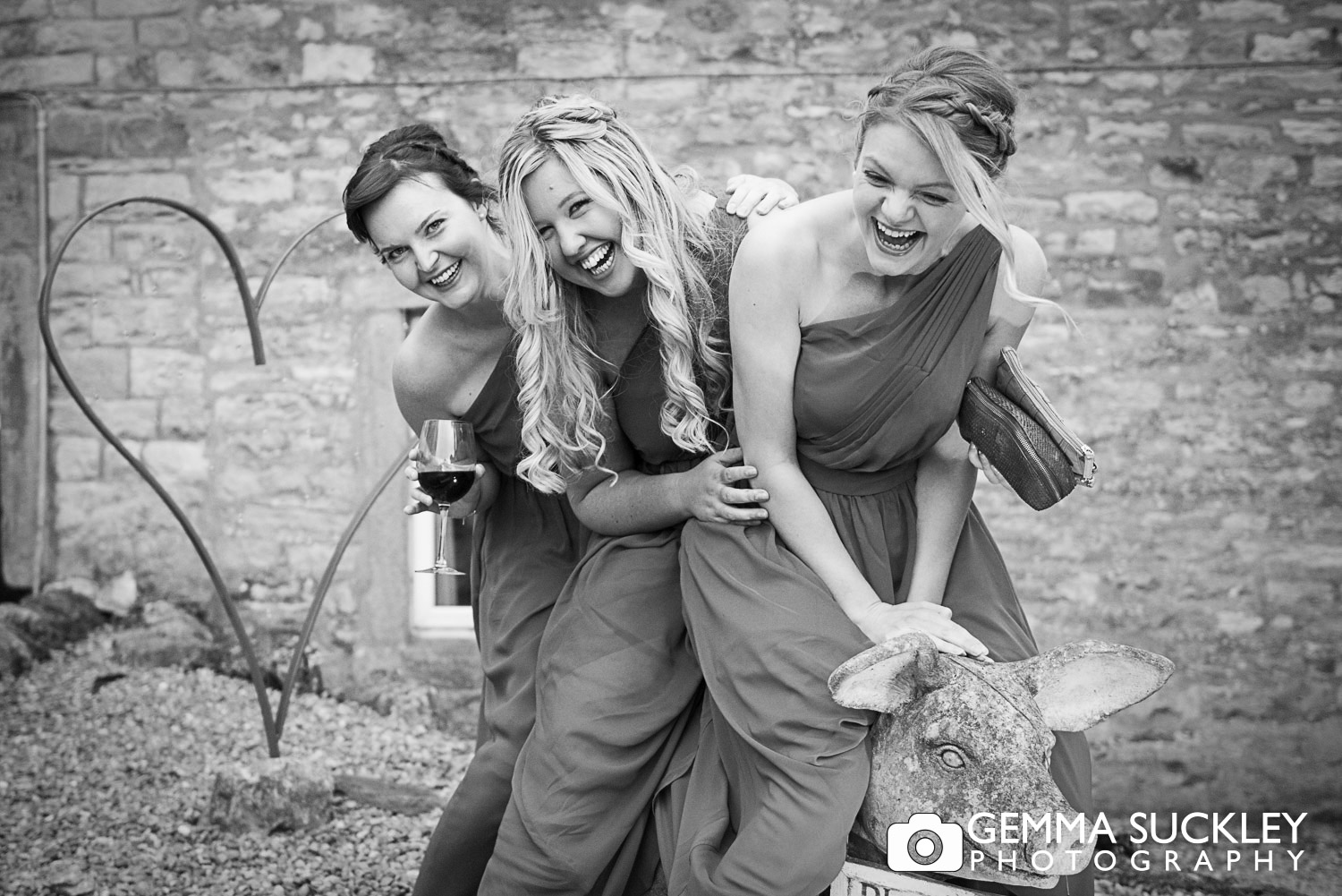 bridesmaids sitting on a pig statue at grassington house