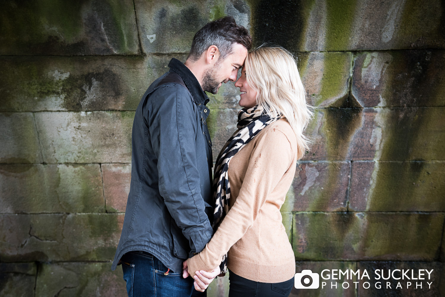 couple holding hands during their engagement photo shoot in burnsall