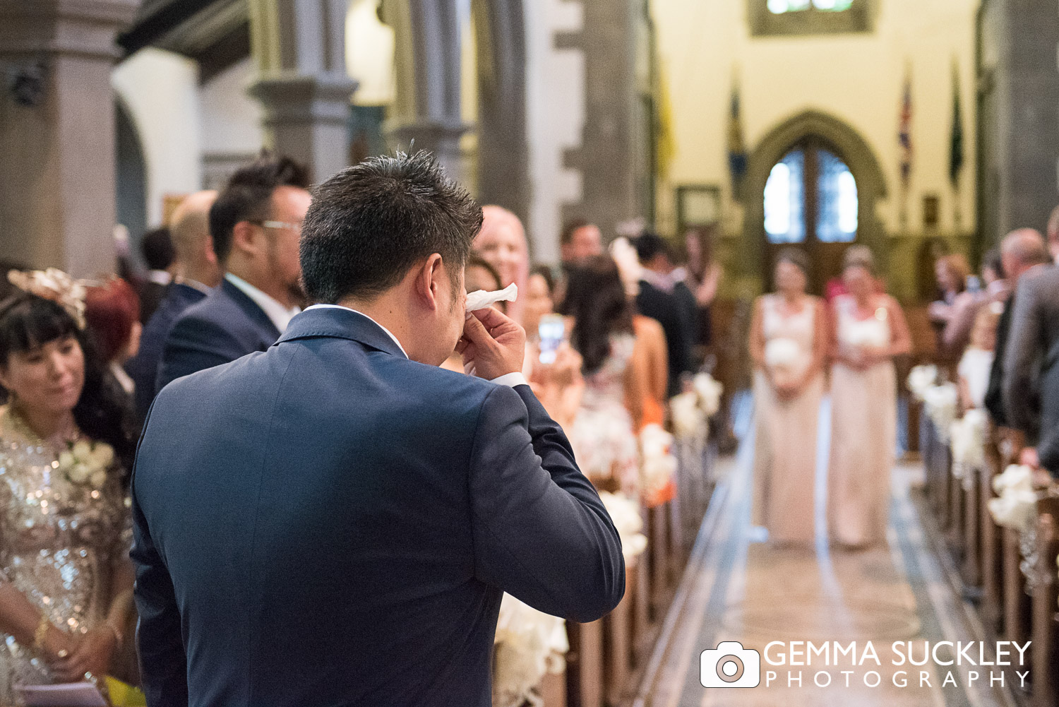 groom crying as his daughers walk down the aisle