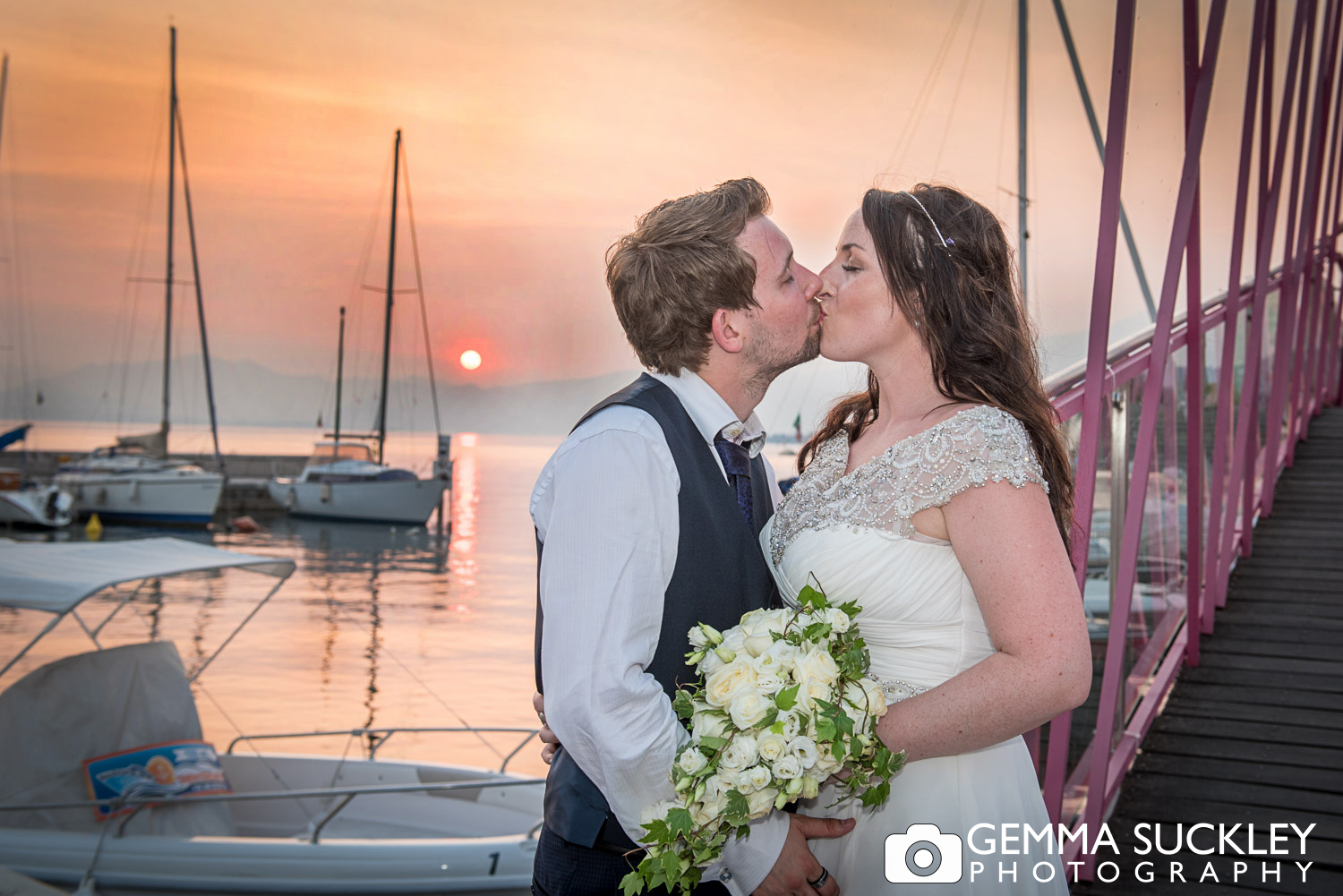 bride and groom kissing as the sun sets in lake garda