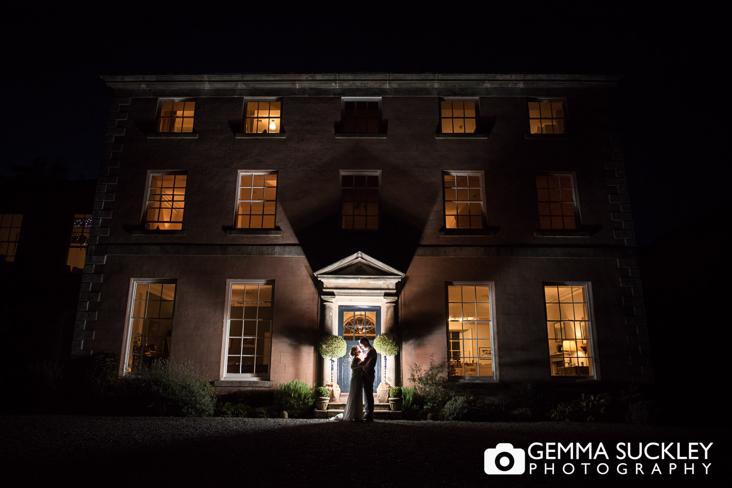 back lit photo of the bride and groom at belmount hall in the dark