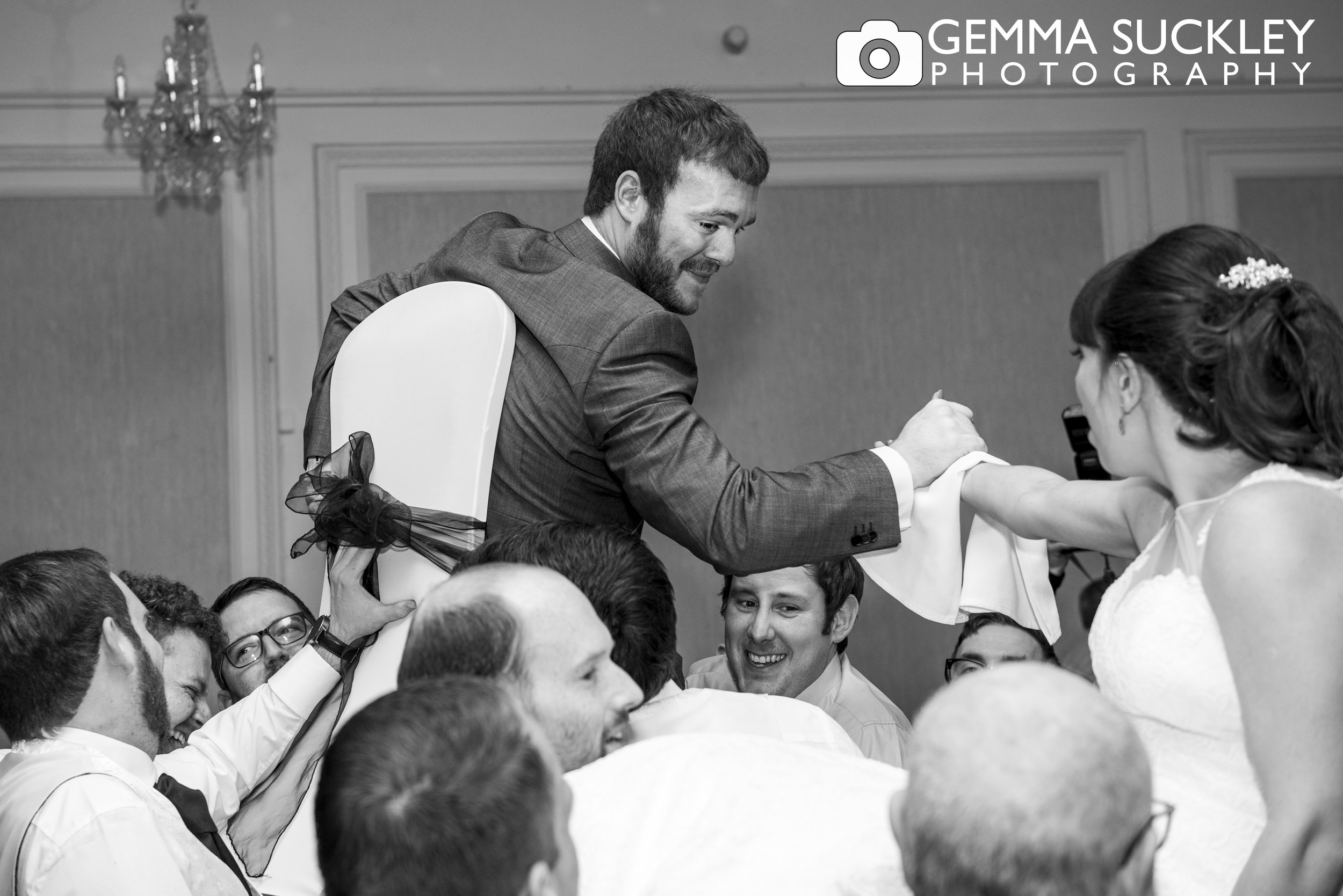 bride and groom lifted on chairs at the swan hotel in harrogate