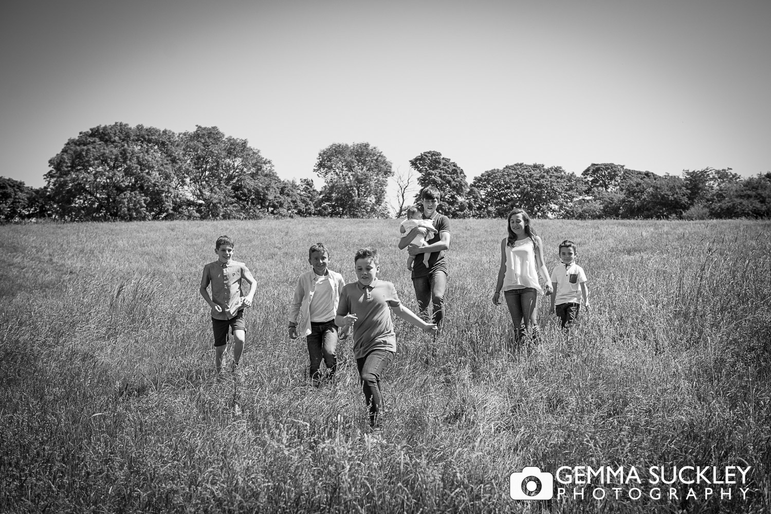 kids walking through a field during a family photo shoot