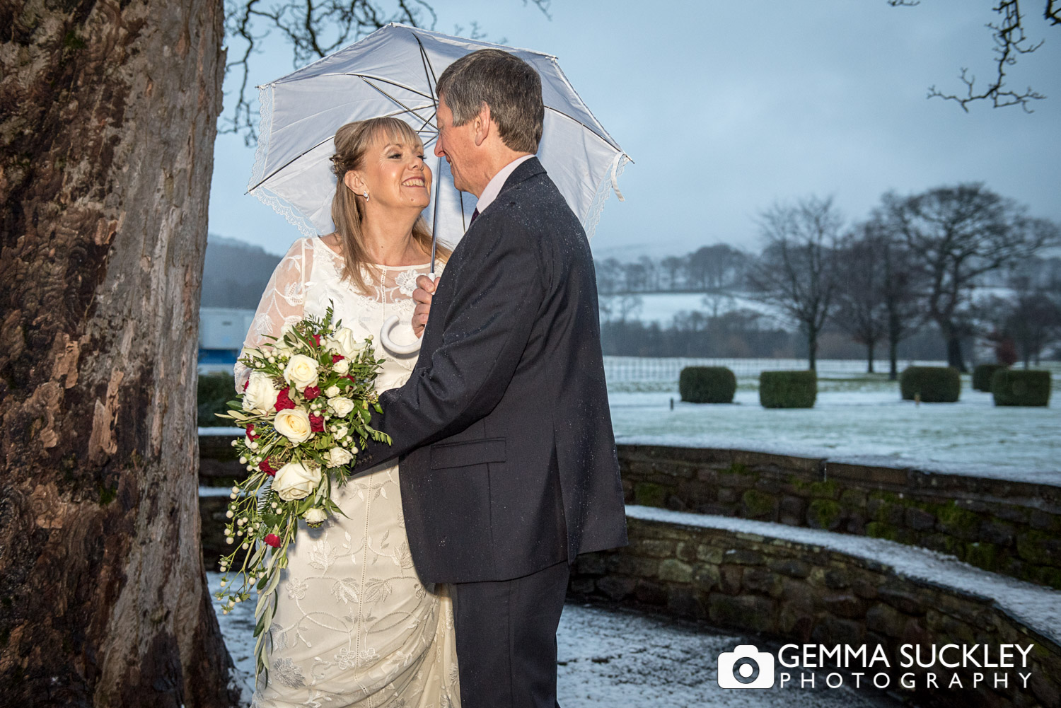 bride and groom in the snow at bolton abbey Devonshire Arms