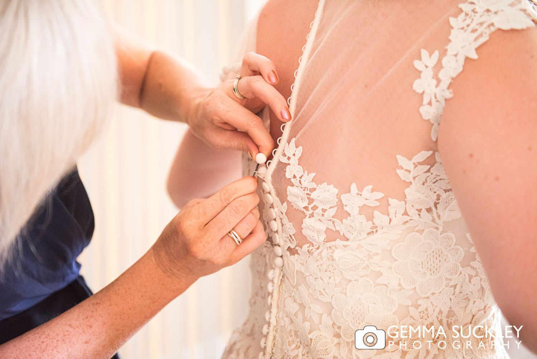 wedding dress buttons being buttoned up