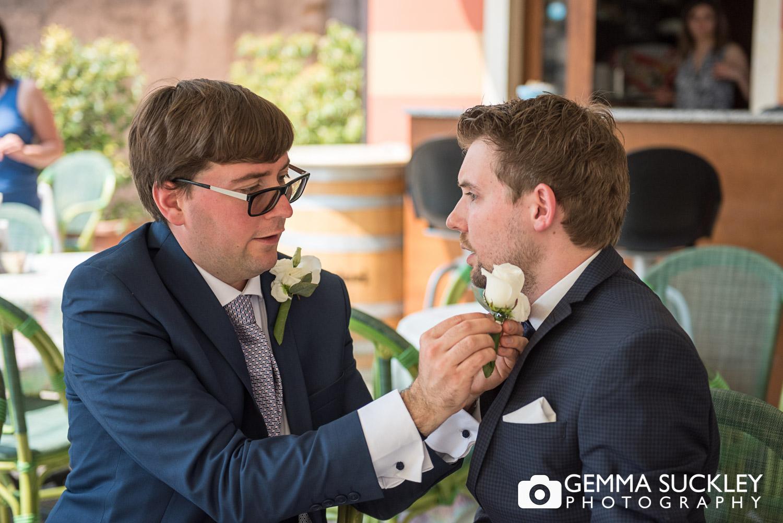 The bestman doing up the groom's tie