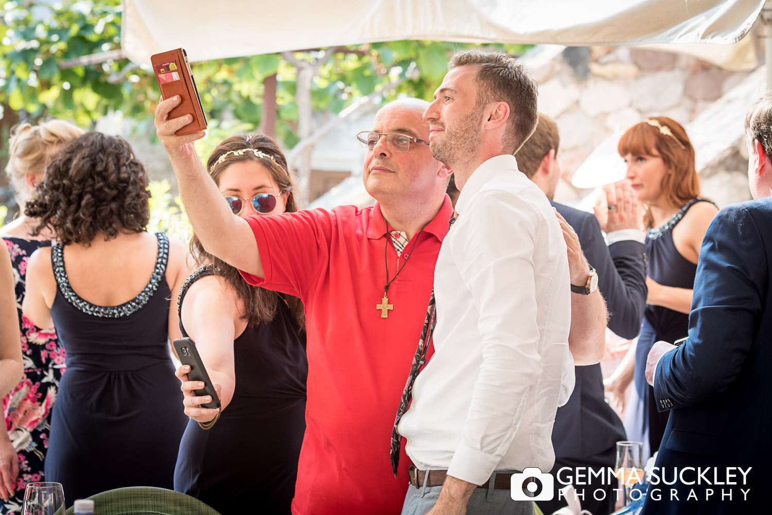 priest taking a selfie with wedding guests