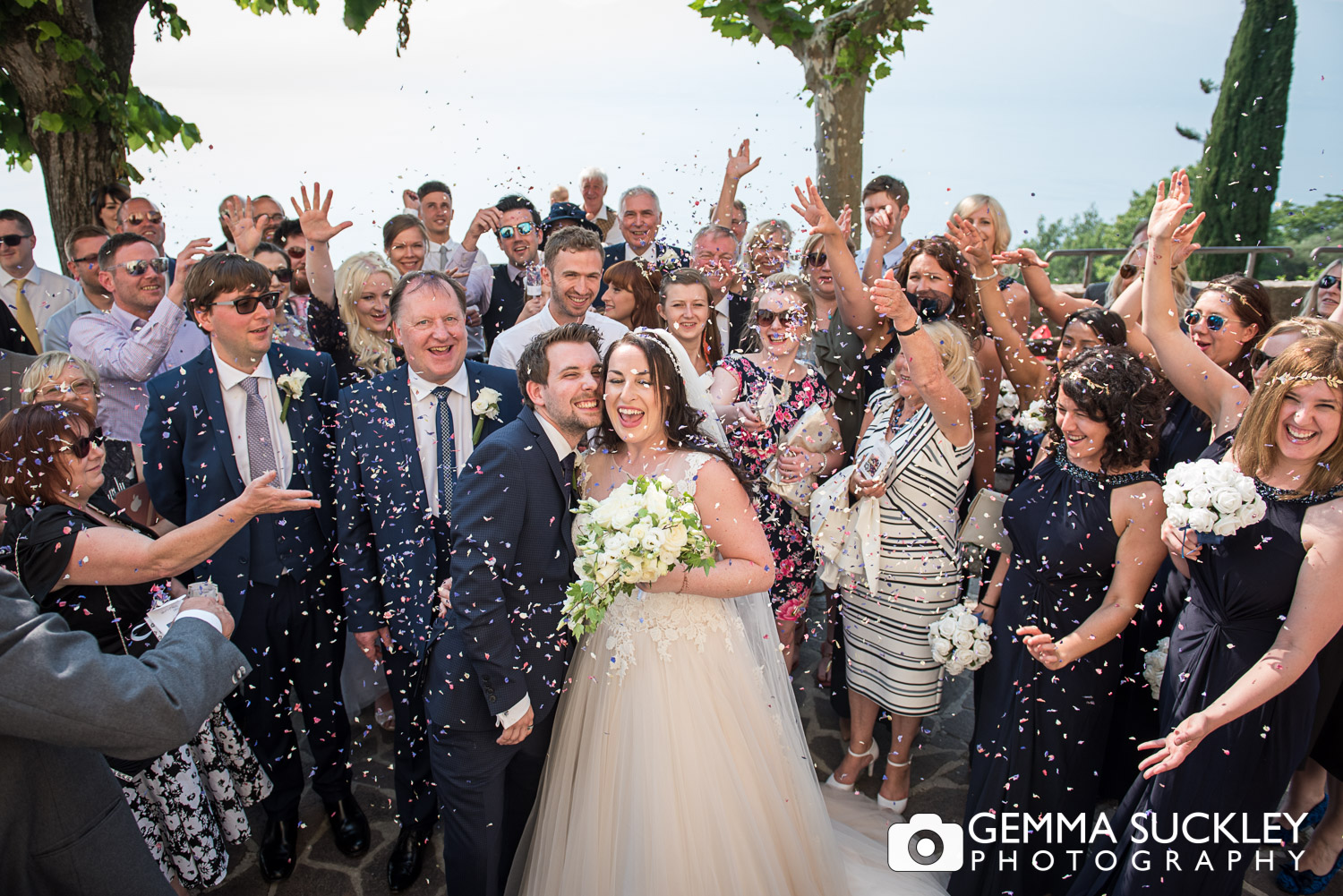 wedding guests throwing confetti at bride and groom