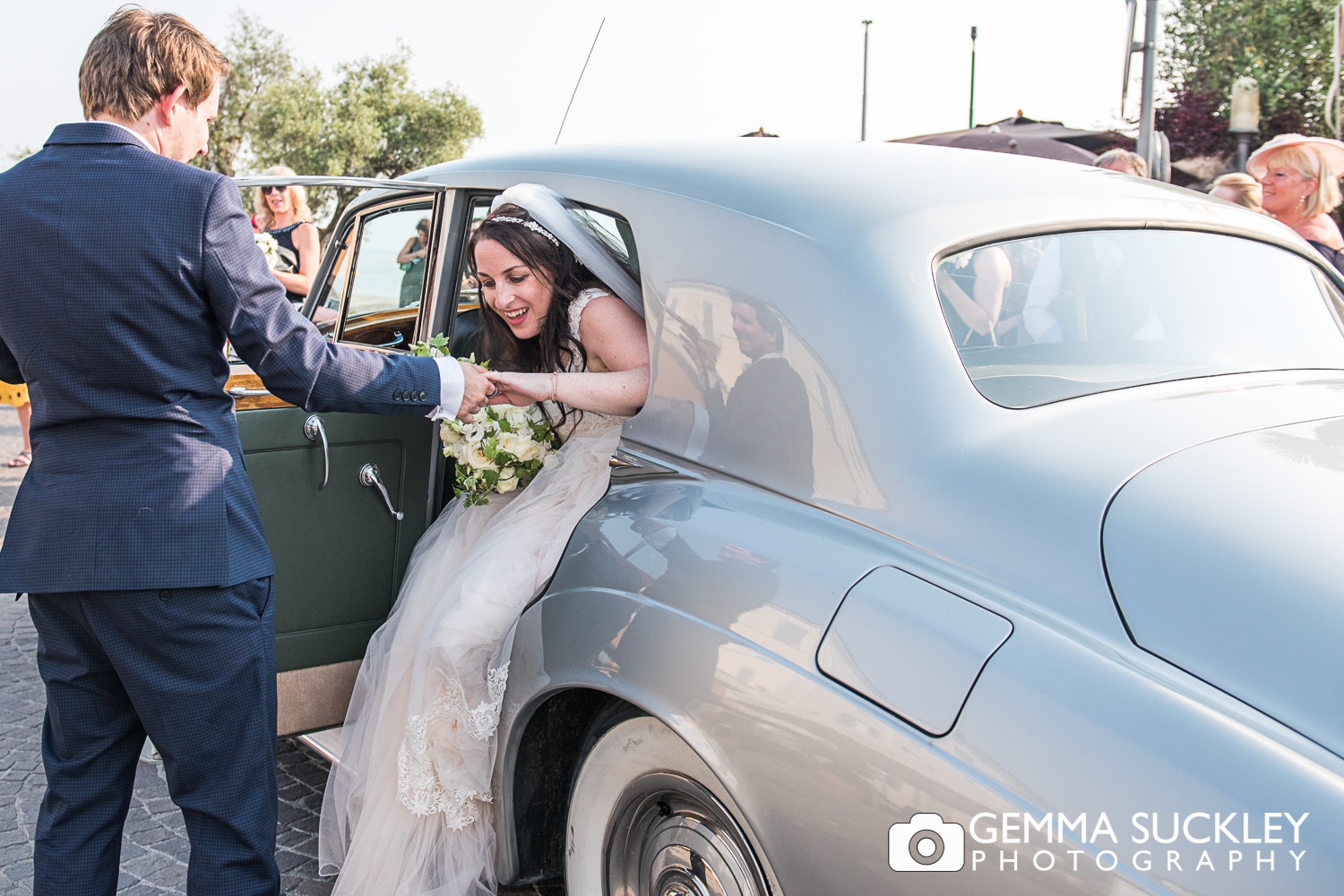 bride and groom getting out of the wedding car
