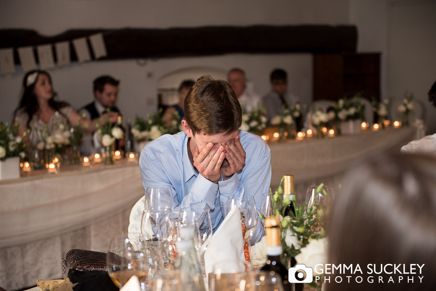Wedding guest covering his face laughing during wedding sppeches