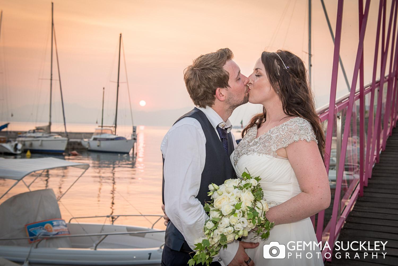 Bride and groom kissing as the sun sets on Lake Garda