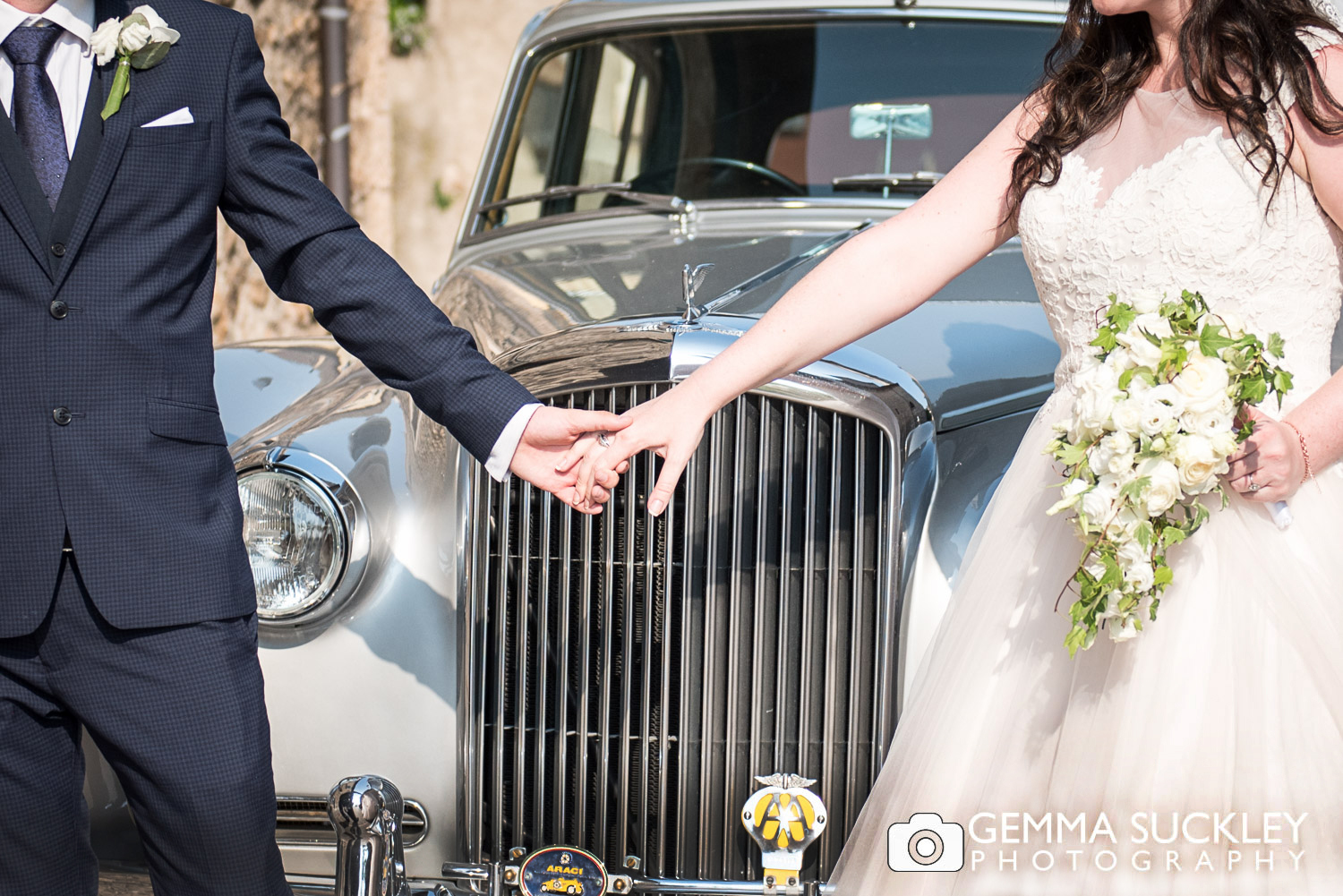 bride and groom posing with wedding car