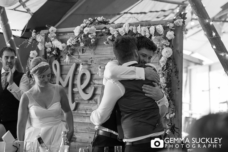 groom hugging his best man at oaklands, East Yorkshire