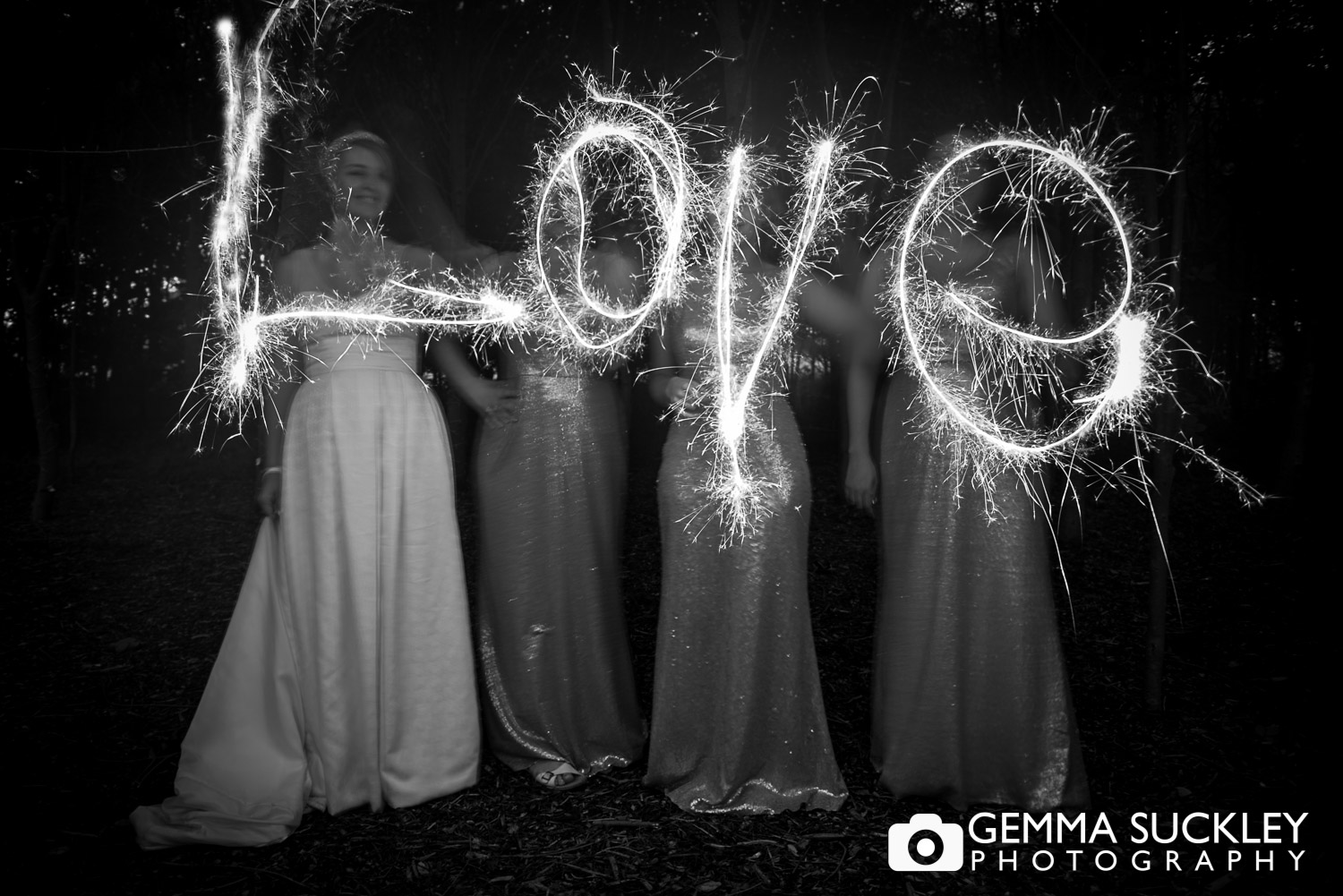 bride and bridesmaid writing love with wedding sparklers