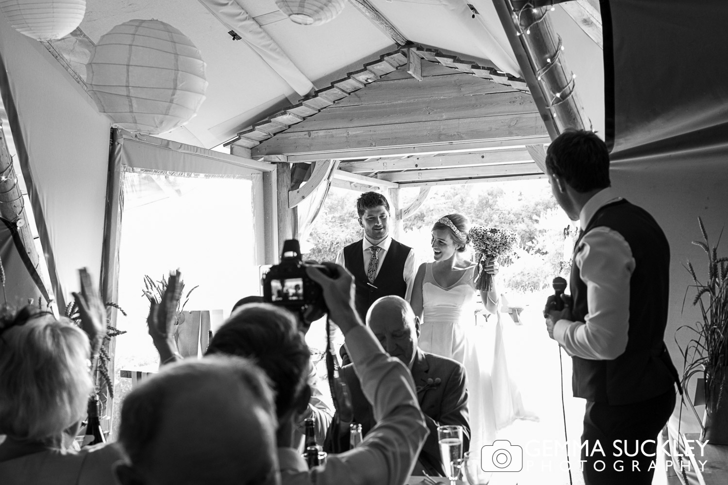 bride and groom walking into the tipi at Oaklands