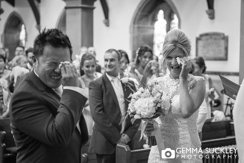 bride and groom wiping their eyes in St John's Church, Bradford